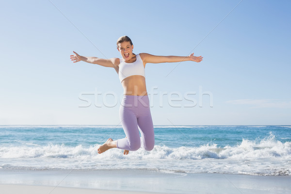 Sporty blonde jumping on the beach with arms out Stock photo © wavebreak_media