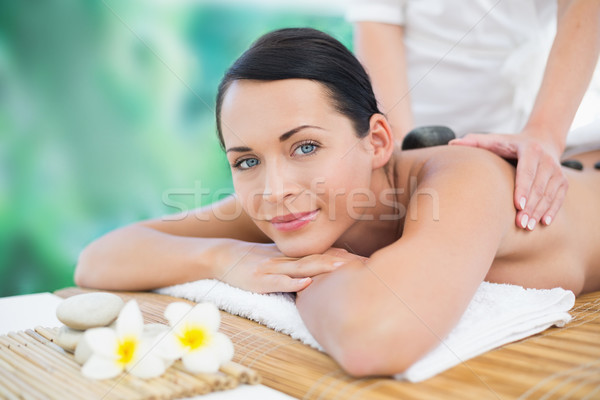 Stock photo: Beautiful brunette enjoying a hot stone massage smiling at camer