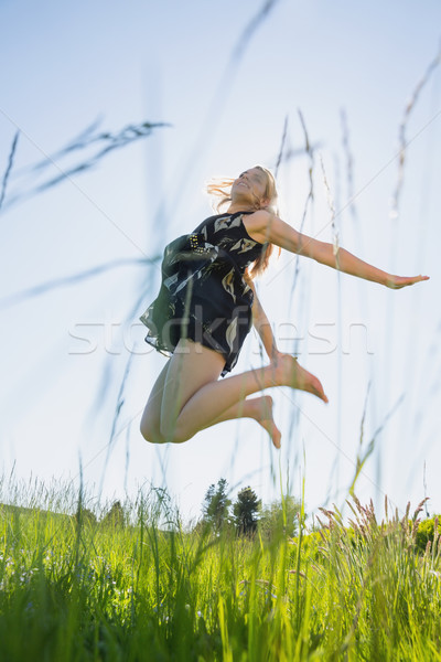 Pretty blonde in sundress jumping up Stock photo © wavebreak_media