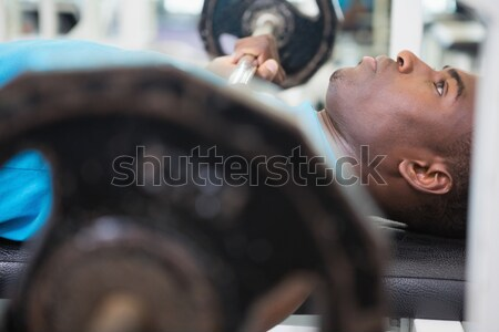 Determined young man lifting barbell in gym Stock photo © wavebreak_media