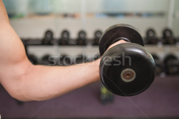 Fit man lifting heavy black dumbbell Stock photo © wavebreak_media