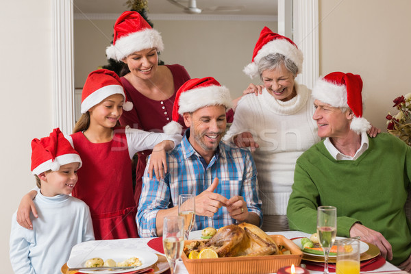 Happy extended family in santa hat at christmas dinner Stock photo © wavebreak_media