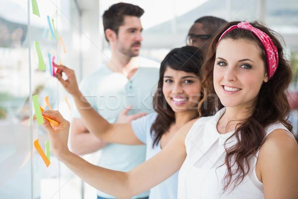 Uśmiechnięty wskazując karteczki biuro spotkanie Zdjęcia stock © wavebreak_media