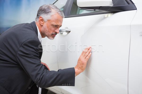 Focused businessman looking at the car body Stock photo © wavebreak_media