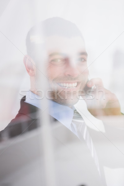 Smiling businessman looking at camera on the phone  Stock photo © wavebreak_media