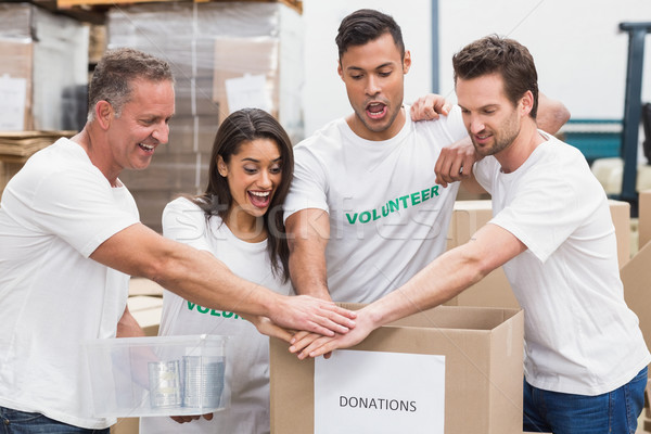 Volunteer team holding hands on a box of donations Stock photo © wavebreak_media