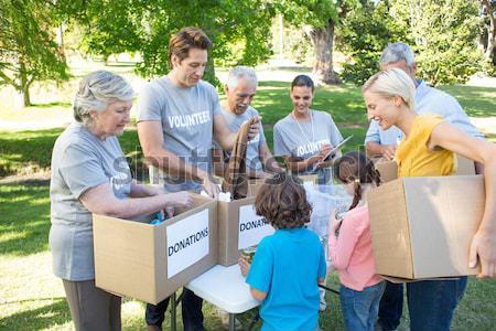 Happy volunteer family separating donations stuffs Stock photo © wavebreak_media