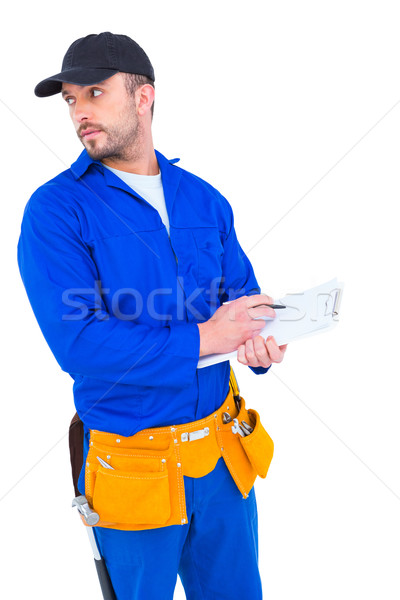 Handyman in blue overall writing on clipboard Stock photo © wavebreak_media
