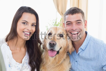 Smiling couple petting their golden retriever Stock photo © wavebreak_media