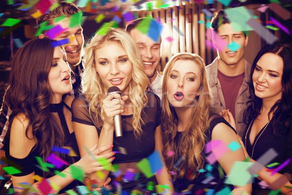 Composite image of happy friends singing karaoke together Stock photo © wavebreak_media