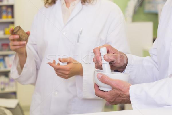 Team of pharmacists holding medicines and mortar Stock photo © wavebreak_media