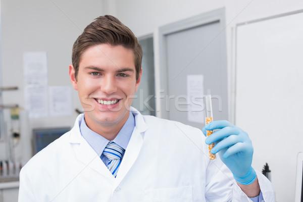 Smiling scientist holding test tube with corn inside  Stock photo © wavebreak_media
