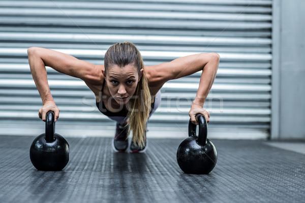 Muscular woman doing pushups with kettlebells  Stock photo © wavebreak_media