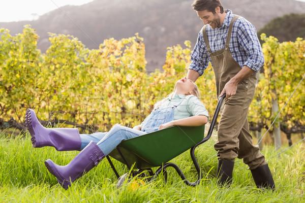 Laughing couple in dungarees pushing a wheelbarrow Stock photo © wavebreak_media