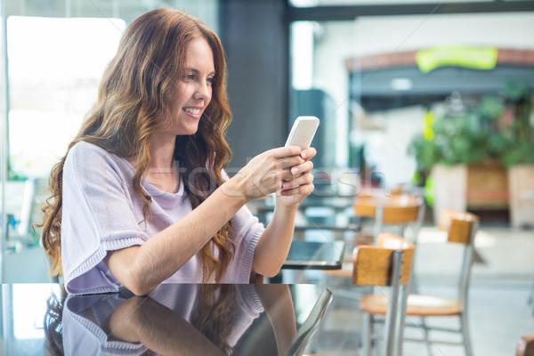 Pretty brunette sending a text Stock photo © wavebreak_media