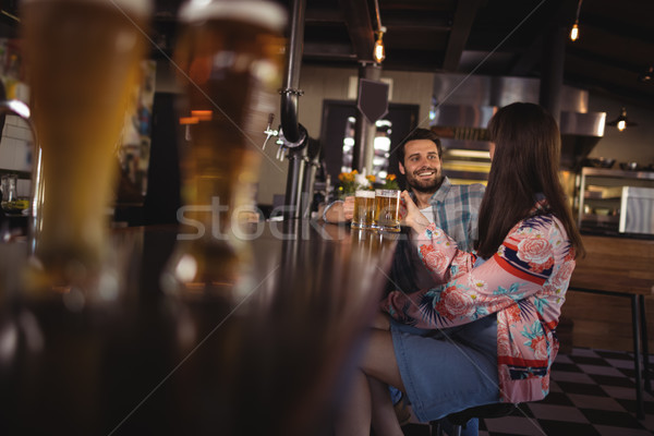 Happy couple interacting while having beer at counter Stock photo © wavebreak_media