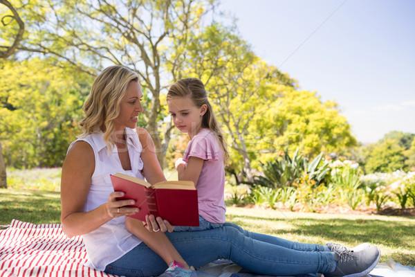 Mother and daughter reading novel in park Stock photo © wavebreak_media