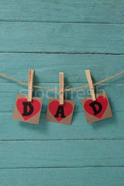 Dad text in heart shapes hanging on green wall Stock photo © wavebreak_media