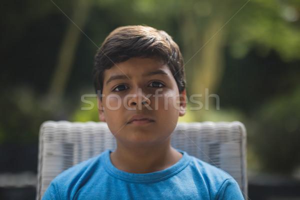 Retrato sério menino sessão cadeira parque Foto stock © wavebreak_media