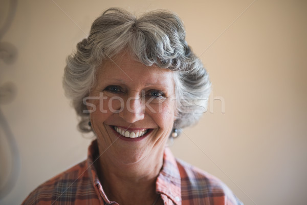 Portrait of smiling senior woman against wall at home Stock photo © wavebreak_media