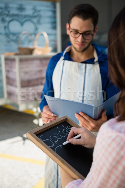 Woman writing menu while coworker reading document Stock photo © wavebreak_media