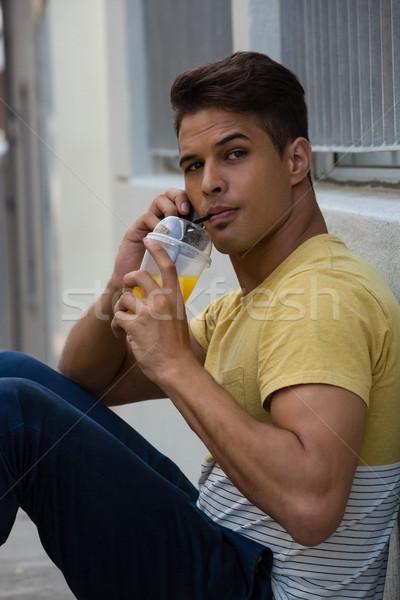 молодым человеком питьевой сока говорить стены Сток-фото © wavebreak_media