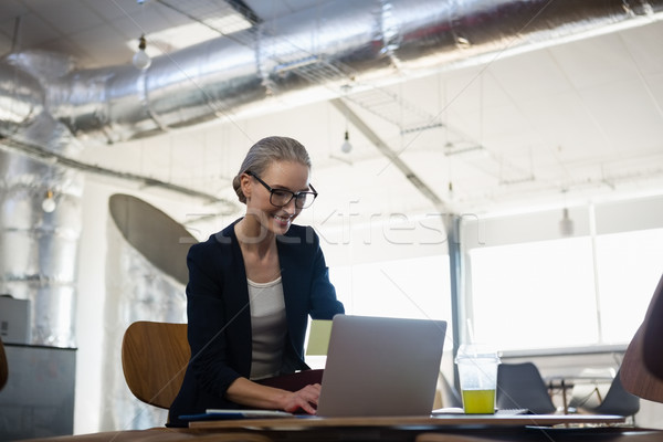 Young woman using laptop in office Stock photo © wavebreak_media