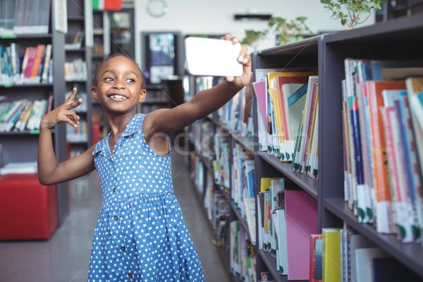 Smiling girl taking selfie by bookshelf in library Stock photo © wavebreak_media