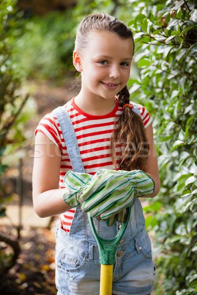 Portrait of smiling girl standing with gardening fork Stock photo © wavebreak_media