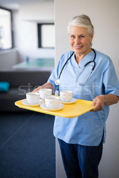 Portrait of senior healthcare worker holding coffee cups Stock photo © wavebreak_media