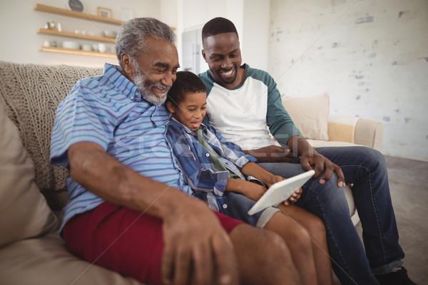 Multi-generation family using digital tablet in living room Stock photo © wavebreak_media