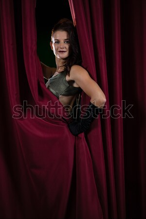 Portrait of female artist posing in front of massive red stage curtain Stock photo © wavebreak_media