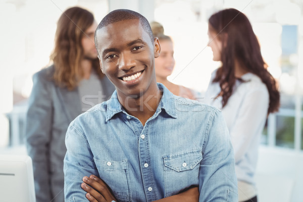 Portrait of smiling man with arms crossed while coworkers discus Stock photo © wavebreak_media