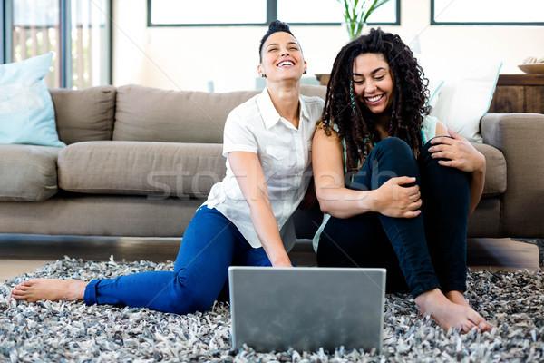 Smiling lesbian couple sitting on rug and using laptop Stock photo © wavebreak_media