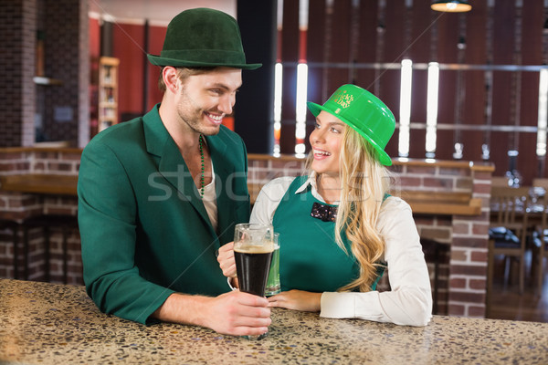 Man and woman looking at each other while holding beers Stock photo © wavebreak_media