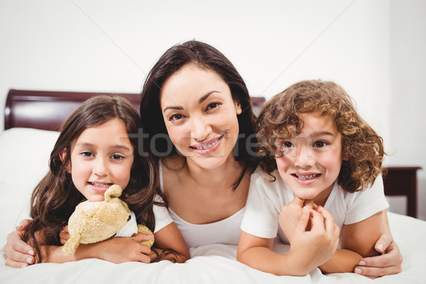 Happy woman with children lying on bed at home Stock photo © wavebreak_media