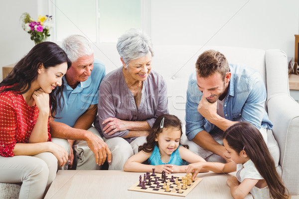 Parents and grandparents looking at girls playing chess Stock photo © wavebreak_media