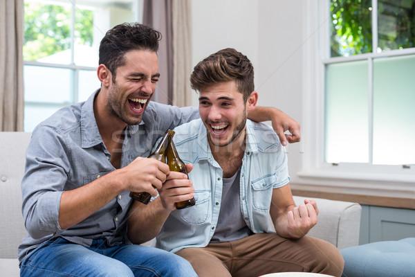 Férfi barátok pirít sör ül kanapé Stock fotó © wavebreak_media