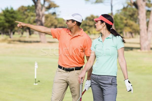 Sonriendo golfista hombre senalando pie mujer sonriente Foto stock © wavebreak_media