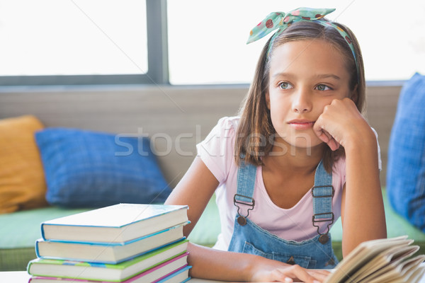 Schoolgirl sitting on table and reading book in library Stock photo © wavebreak_media