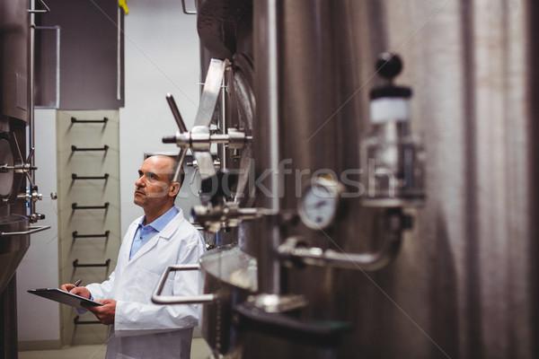 Manufacturer looking at storage tanks in brewery Stock photo © wavebreak_media