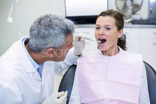 Dentist examining a woman with tools Stock photo © wavebreak_media