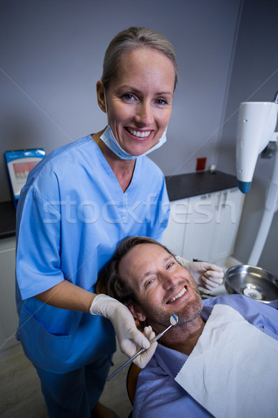 Smiling dentist examining a young patient with tools Stock photo © wavebreak_media