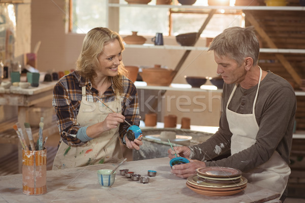 Stock photo: Smiling potters painting on bowl in pottery workshop