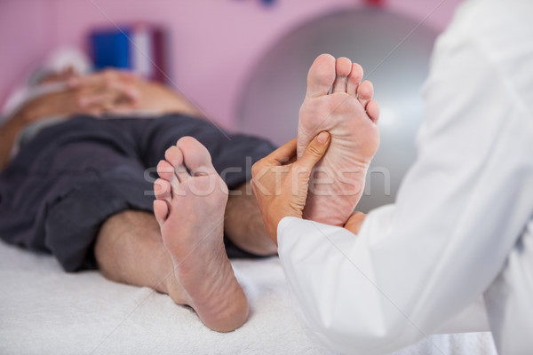 Senior man receiving foot massage from physiotherapist Stock photo © wavebreak_media