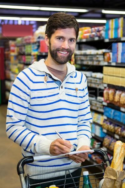 Człowiek piśmie notatnika zakupy spożywczy sekcja Zdjęcia stock © wavebreak_media