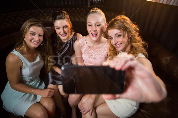 Gülen arkadaşlar cep telefonu kadın bar Stok fotoğraf © wavebreak_media