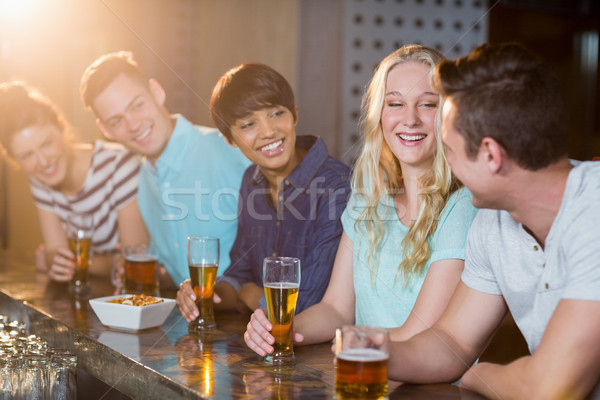 Group of friends interacting with each other while having beer at bar counter Stock photo © wavebreak_media