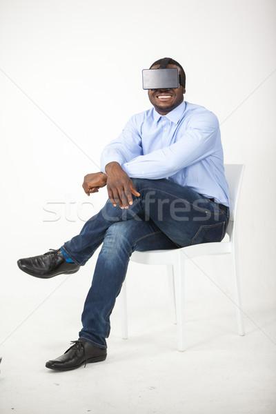 Man sitting on chair and using virtual reality headset Stock photo © wavebreak_media