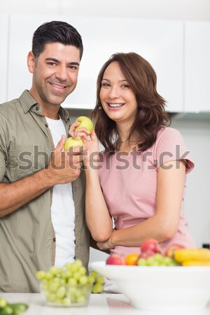 Loving couple eating fruit lying on their bed  Stock photo © wavebreak_media
